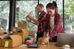 Startup small business owner working with computer at workplace. Freelance men & women seller check product order, packing goods for delivery to customer Stock Images