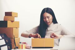 Startup small business owner working with computer at workplace. Freelance woman seller check product order, packing goods for delivery to customer. Online royalty free stock images