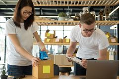 Startup small business owner working with computer at workplace. Freelance men & women seller check product order, packing goods for delivery to customer Royalty Free Stock Image