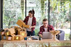 Startup small business owner working with computer at workplace. Freelance men & women seller check product order, packing goods for delivery to customer Royalty Free Stock Images