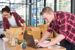 Startup small business owner working with computer at workplace. Freelance men & women seller check product order, packing goods for delivery to customer Stock Photo