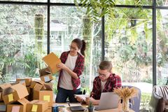 Startup small business owner working with computer at workplace. Freelance men & women seller check product order, packing goods for delivery to customer Royalty Free Stock Photo