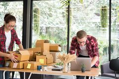 Startup small business owner working with computer at workplace. Freelance men & women seller check product order, packing goods for delivery to customer Stock Photography