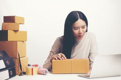Startup small business owner working with computer at workplace. Freelance woman seller check product order, packing goods for delivery to customer. Online stock photos