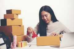 Startup small business owner working with computer at workplace. Freelance woman seller check product order, packing goods for delivery to customer. Online royalty free stock image