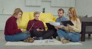 Startup team sitting on floor and working together stock footage