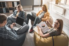 Startup team working with comfort. Tranquil men and women sitting with comfort in their modern office. Girl with project documentation in hand looking at camera Royalty Free Stock Photos