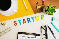 Startup word on desk office background with supplies. Stock Image
