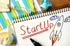 StartUp word written on the notepad. Royalty Free Stock Photo
