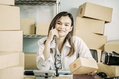 Startup working at workplace business owner smile happily is preparing to deliver packed into cardboard to deliver customers, stock photo