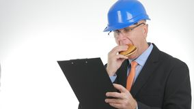 Starved Engineer Enjoy a Tasty Snack and Read Documents. Starved Engineer Eat a Tasty Snack and Read Documents from a Clipboard royalty free stock photography