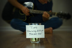 Starving artist guitarist street performer with tip cup jar royalty free stock images