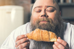 Starving fat guy enjoying smell of pastry Stock Photos