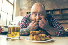 Starving fat man is shocked about fried chicken Stock Photo