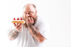 Starving fat man staring at mouthwatering dessert Stock Photos