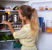 Starving girl searching food on fridge Stock Images