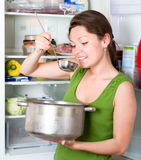 Starving woman eating near refrigerator Royalty Free Stock Images