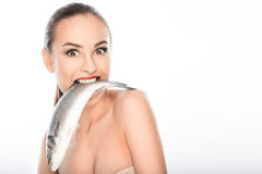 Starving woman holding fish in mouth Royalty Free Stock Photos