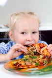 Starving young girl eating Stock Photography