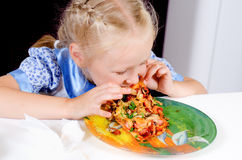 Starving young girl eating Stock Image