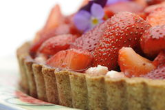 Starwberry tart close-up. Close-up of a strawberry tart with tasty crust and purple flowers Stock Photography
