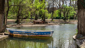 Stary łódkowaty obsiadanie na małym jeziorze w parku Zdjęcia Stock