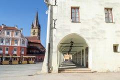 Stary, średniowieczny, biały budynek z korytarzem z kilka archways, i kościelny wierza w tle w Sibiu, Rumunia fotografia royalty free