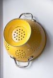 Stary żółty colander obwieszenie na ścianie Zdjęcia Royalty Free