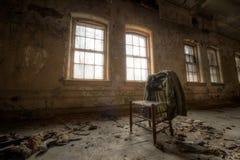 Stary żakiet i krzesło w zaniechanym budynku obraz stock