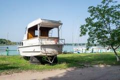 Stary żeglowanie jacht na ziemi Stary bielu silnika jacht wyrzucać na brzeg przy a zdjęcia stock