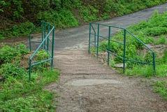 stary żelazo most na szarej asfaltowej drodze w zielonej trawie zdjęcie stock