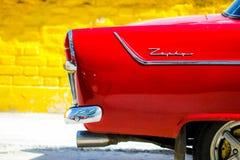 Stary ale patrzejący jako brandnew błyszczący czerwony samochód w Kuba obrazy royalty free