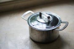 Stary aluminiowy stali nierdzewnej kucharstwa garnek na kuchennym stole Obrazy Stock