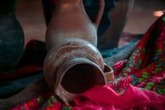 Stary antyczny ceramical gliniany dzbanek na tkaninie fotografia stock