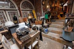 Stary antykwarski sklep z wiele rocznika naczynie, wystrój, drewniany meble, retro maszyna do pisania i wiele szczegóły, Fotografia Stock