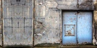 Stary betonowy budynek z błękitnymi drzwiami obrazy stock