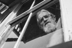 Stary bezwolny spoglądanie myśleć mężczyzna łamający okno Obrazy Royalty Free