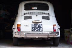 Stary biały Fiat 500 L samochodowi stojaki w ciemnym garażu Zdjęcia Stock