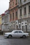Stary biały Volga samochód parkujący na brukującej bocznej ulicie w Kamianets-Podilsky Obraz Stock