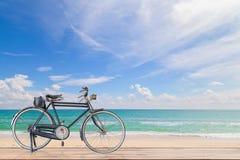 Stary bicykl na drewnie z Turkusowego morza, piękną plażą a morze Obrazy Stock