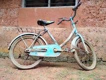 Stary bicykl umieszczający tło stara błoto ściana zdjęcia stock
