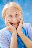 Portret zdziwiona starsza kobieta z rękami na twarzy na błękitnych półdupkach Fotografia Royalty Free