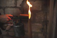 Stary blowtorch z ogieniem w męskich rękach obraz stock