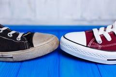Stary brudny podławy i nowy nienoszony sneakers zakończenie na koloru backg Zdjęcia Royalty Free