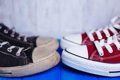 Stary brudny podławy i nowy nienoszony sneakers zakończenie na koloru backg Obrazy Royalty Free