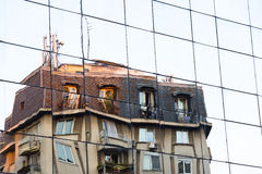 Stary budynek odbija na nowożytnej szklanej fasadzie zdjęcie stock