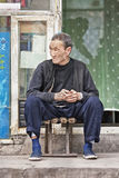 Stary Chiński mężczyzna siedzi przed jego domem w hutong, Pekin, Chiny Obraz Stock