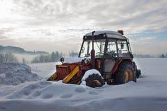 Stary ciągnik pod śniegiem Śnieżna klęska w transporcie Zamarznięty silnik diesla Fotografia Stock