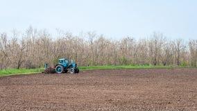 Stary ciągnik w polu orze ziemię Wiosna krajobraz wieś, gospodarstwo rolne Zdjęcie Stock