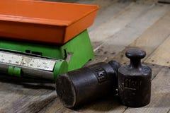 Stary ciężar i ciężary na drewnianym stole Stara używać kuchni skala Obrazy Stock